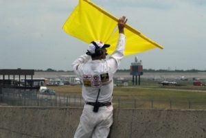 Corner worker at Texas World Speedway holding up a double yellow