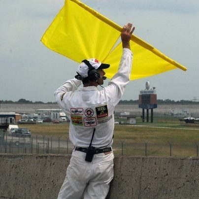 Image of a corner worker holding up a double yellow flag